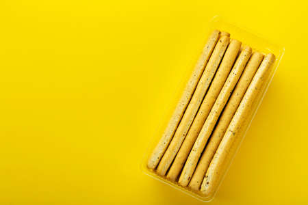 Homemade Italian Grissini Bread Sticks on a yellow background. Space for text. Top view.