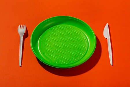 Plastic set of disposable tableware consisting of a plate, knife and fork on an orange background.