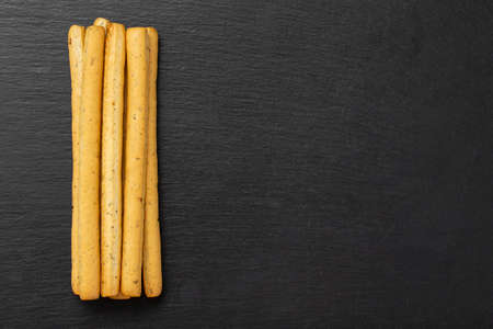 Homemade Italian Grissini Breadsticks on a black background. Traditional italian snack with herbs. Space for text. Top view.