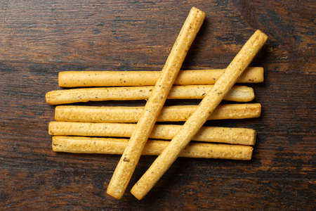 Homemade Italian Grissini Breadsticks on a wood background. Traditional italian snack with herbs. Space for text. Top view. 写真素材