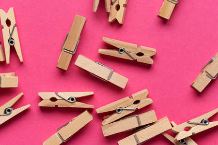 Many wooden clothespin on pink background. Top view.