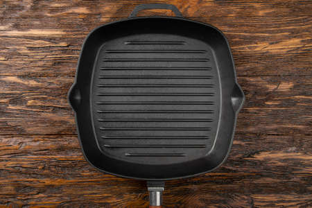 An empty black cast iron grill pan for cooking delicious meat. Wood background. Space for text. Top view.