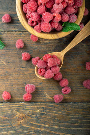 Fresh raspberries in a wooden plate with leaves. The berries are scattered on a wooden table. Harvesting concept 写真素材