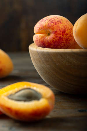 Fresh apricots in a wooden plate. Fruits are scattered on a wooden table. Harvesting concept