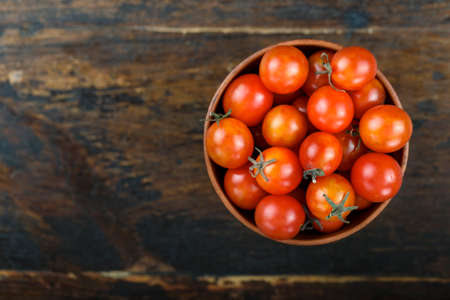 cherry tomatoes in a clay plate on a brown wooden background. view from above