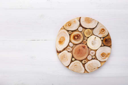Empty round cutting board on a white wooden table. Top view.