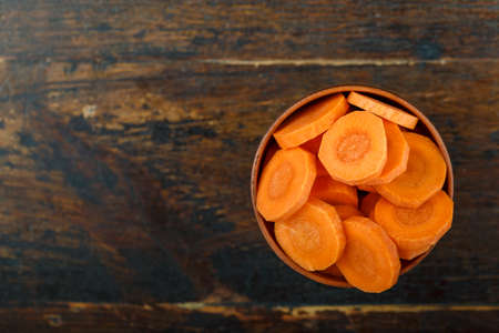 Sliced carrots in a bowl on a wooden background. Vegetable, ingredient and staple food. Healthy food. 写真素材