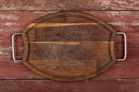 Empty oval cutting board with iron handles on a red wooden table. Top view.