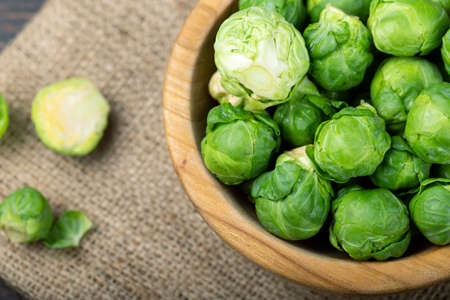 Brussels sprouts in a wooden bowl. Harvesting. Top view.