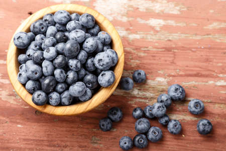 Fresh blueberries in a wooden bowl. Healthy and dietary food concept. Derefensky background.