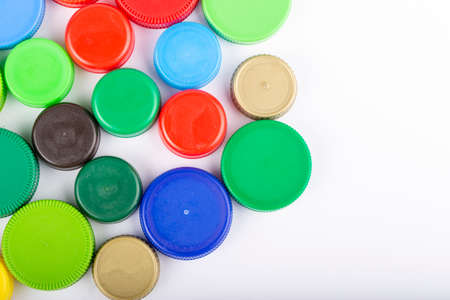 Many multi-colored plastic bottle caps on a white background. Recycling concept. Text for space. Top view. 写真素材