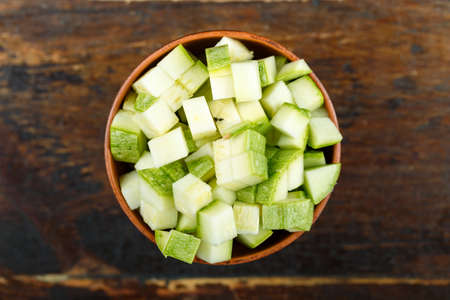 Sliced zucchini in a bowl on a wooden background. Vegetable, ingredient and staple food. Healthy food.