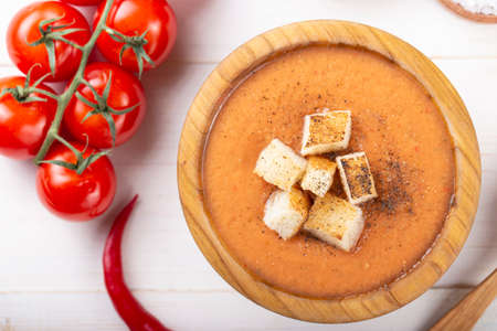Spicy Homemade Gazpacho Soup Ready to Eat. Tasty appetizing summer tomato soup puree on a white wooden table.