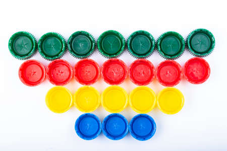 Plastic multi-colored bottle caps are arranged in rows on a white background. Recycling and reuse concept. 写真素材
