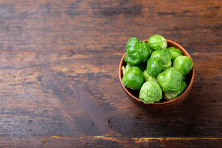 Bunch of fresh Bruxelles sprouts in a cup on wooden background. Healthy vegetables.