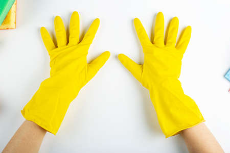 Hand in a latex glove in yellow isolated on white. Hand gesture or sign isolated on white. Cleanliness and cleaning concept. File contains clipping path.