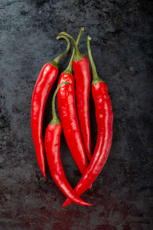 Pods of red chili peppers on a dark background close-up - top view 写真素材
