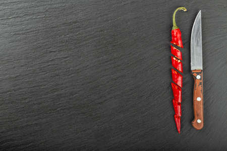 Red chopped chile peppers and a knife on a black slate board. Spicy food concept. Space for text. Top view. 写真素材
