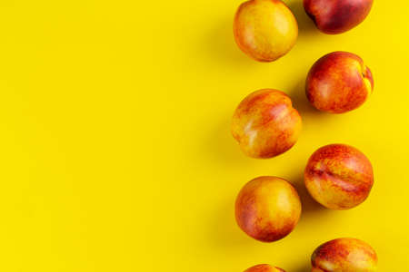 Ripe nectarine on a yellow background. Fresh fruits. Top view. Space for text.