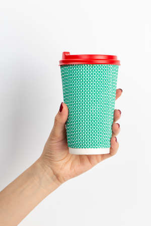 Female hand holding disposable coffee cup green color on white background. Close-up.