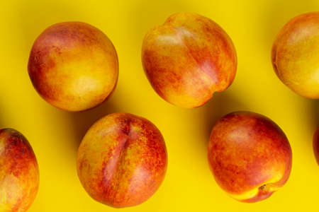 Ripe nectarine on a yellow background. Fresh fruits. Top view.