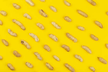 Peanuts pattern isolated on a yellow backround. Repetition concept. Top view 写真素材