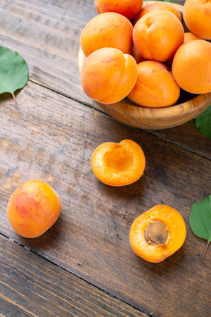 Delicious ripe apricots in a clay bowl on the table close-up. Healthy fruits. 写真素材