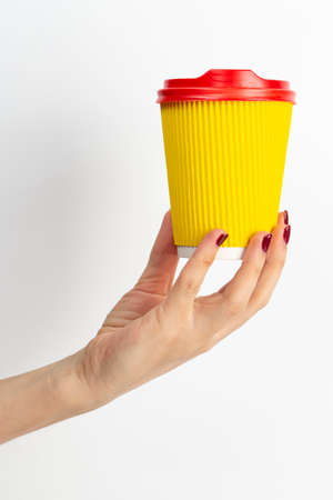 Female hand holding disposable coffee cup yellow color on white background. Close-up.