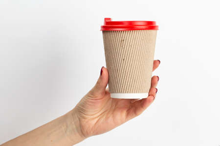 Female hand holding disposable coffee cup brown color on white background. Close-up. 写真素材