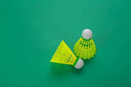 Two badminton shuttlecock on a green background. Minimalism. Concept summer entertainment. Sport games. Space for text.