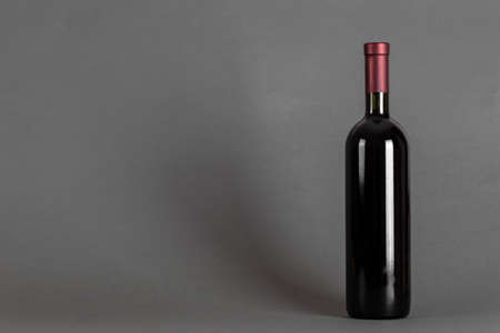 Closed bottle of wine on a gray background. Wine drinking culture concept. Space for text.