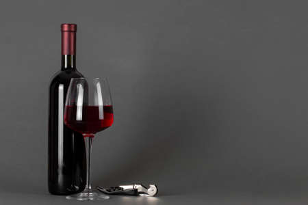 Red wine bottle, corkscrew and glass on a gray background. Wine drinking culture concept. Space for text.