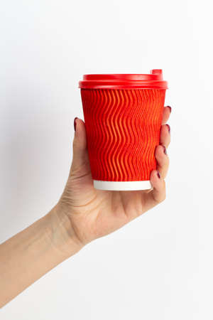 Female hand holding disposable coffee cup red color on white background. Close-up. 写真素材