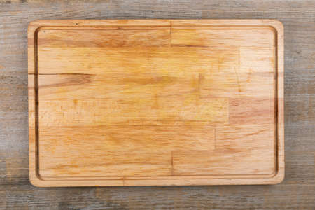 Empty cutting board on a wooden table. Space for text. View from above.