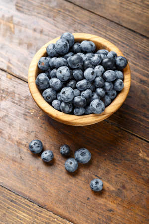 Freshly picked blueberries in wooden bowl on wooden background. Concept of healthy and dieting eating. Tasty food.