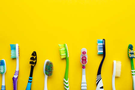 Toothbrushes on a yellow background. Health care, dental hygiene. Space for text. Top view.