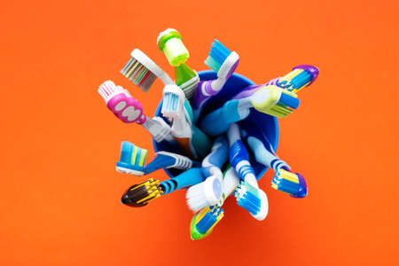 Toothbrushes in a cup on a orange background. Health care, dental hygiene. Space for text. Top view.