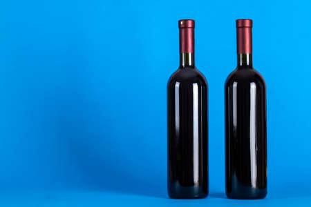 Two corked bottles of wine on a blue background. Wine drinking culture concept. Space for text. Top view.