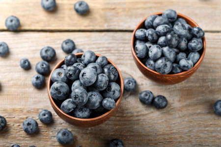 Freshly picked blueberries in clay bowl on wooden background. Concept of healthy and dieting eating. Tasty food.