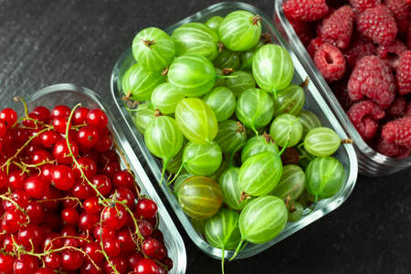 Assorted berries of raspberries, gooseberries and red currants in glass bowls on a black table. Summer harvest of berries