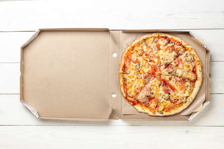 Pizza in a cardboard box against a white background. Space for text. View from above. Pizza delivery. Pizza menu.