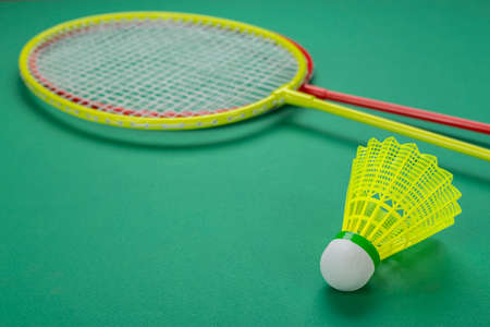 Shuttlecock and racket for playing badminton on a green background. Minimalism. Concept summer entertainment. Sport games
