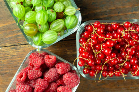 Assorted berries of raspberries, gooseberries and red currants in glass bowls on a wooden table. Top viewn