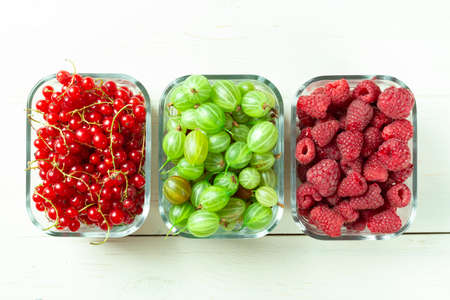 Assorted berries of raspberries, gooseberries and red currants in glass bowls on a white table. Summer harvest of berries 写真素材