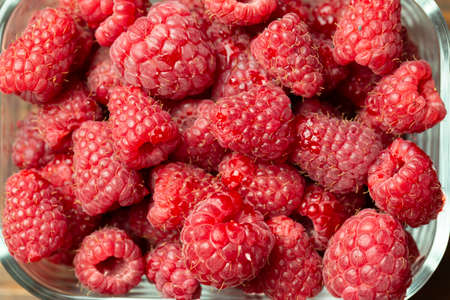 Ripe raspberry in a glass plate, place for text, top view, summer harvest of berries