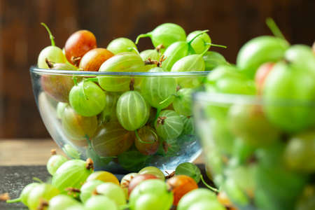 Ripe gooseberry in a glass plate, place for text, top view, summer harvest of berries