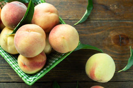 Ripe peaches in basket on wooden background. Home harvest from your own garden. Healthy eating.