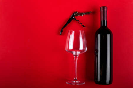 Bottle of red wine and an empty wine glass with a corkscrew next to it. Composition on a red background. Romantic mood. Space for text. Top view.