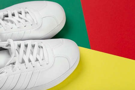 Women's stylish sneakers on a colorful background. Lifestyle sneaker sport shoe. Space for text. Top view. Casual shoes. Reklamní fotografie