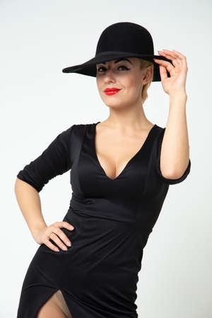 A mysterious girl in a black dress with a neckline and a black hat, a photo in the studio, a vertical photo